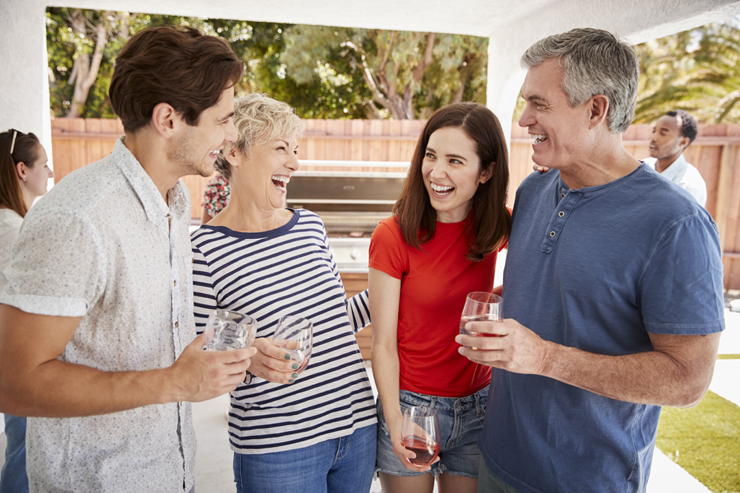Parents and adult children standing with drinks in garden
