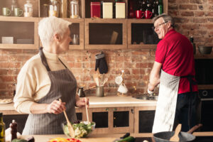 Positive retired couple at kitchen, preparing for dinner, smiling to each other