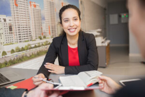 Portrait of friendly mixed-race woman smiling happily while talking to client in real estate agency