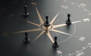 3D illustration of a golden compass rose over black background with five pawns. Business strategy and guidance concept