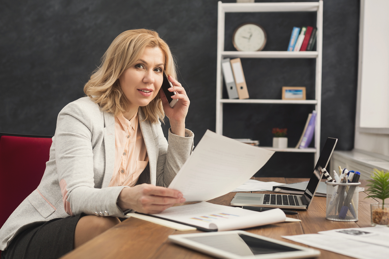 Successful smiling businesswoman at work consulting on phone and writing notes while sitting at her working place in office, copy space