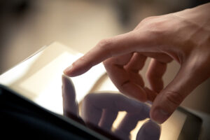 Man hand touching screen on modern digital tablet pc. Close-up image with shallow depth of field focus on finger.