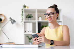 Portrait of content young marketing specialist in yellow dress sitting with smartphone in modern office