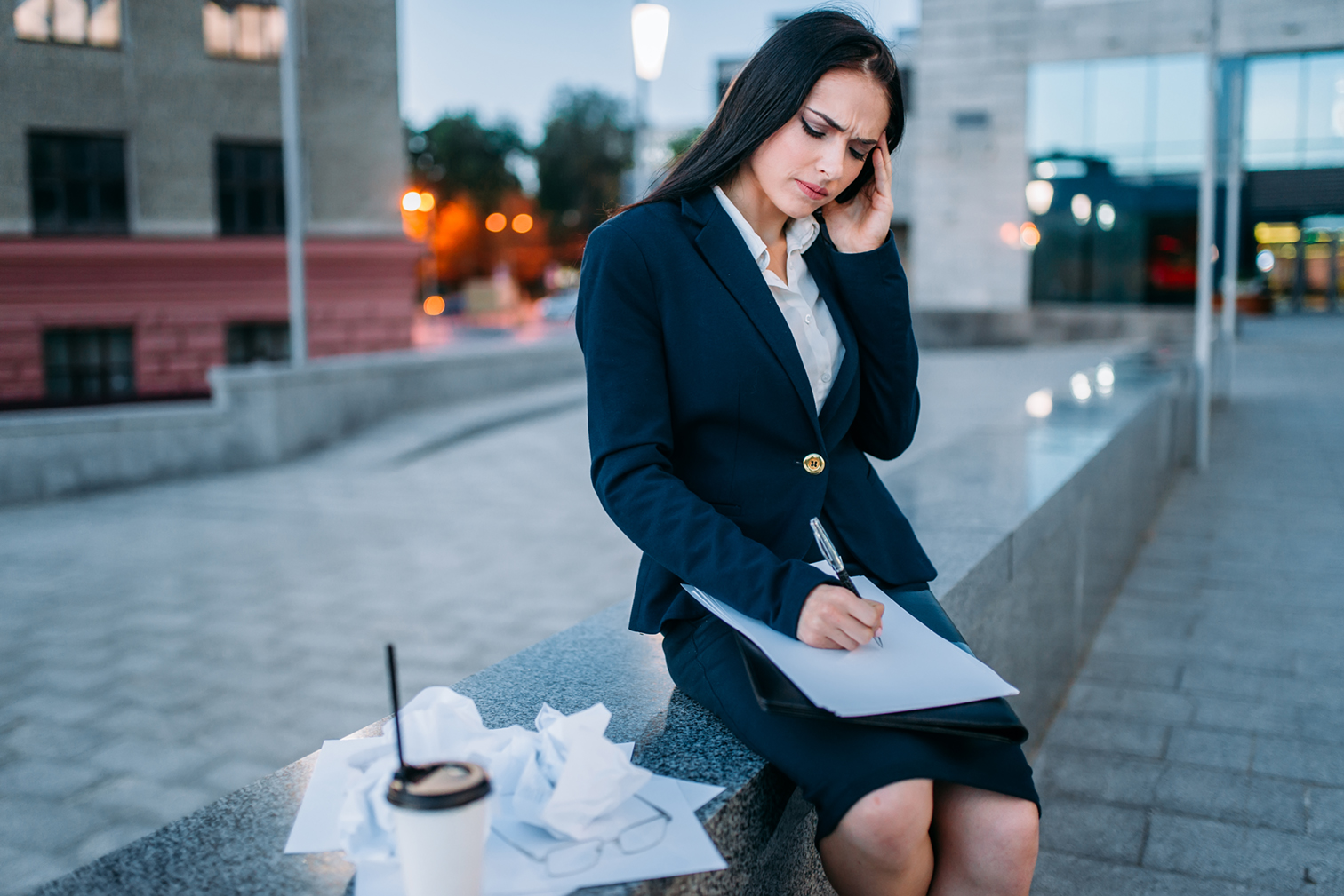 Tired businesswoman works outdoor, financial statements, business center on background. Modern building, cityscape. Female businessperson